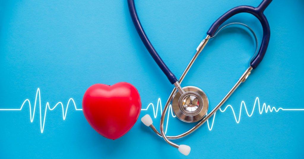 red rubber heart and stethoscope on blue background with cardiogram, health concept; blog: Can Peripheral Artery Disease Affect Heart Health?